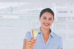 Mulher de negócios moreno que aumenta um vidro do champanhe Imagens de Stock Royalty Free