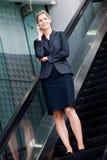 Mulher de negócios na escada rolante imagem de stock