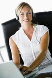 Mulher de negócios na mesa com auriculares Fotografia de Stock Royalty Free