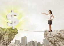 Mulher de negócios na montanha da rocha com uma marca de dólar Foto de Stock Royalty Free