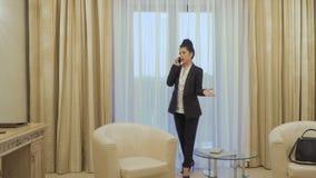 A mulher de negócios nervosa fala no telefone video estoque