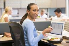 Mulher de negócios no compartimento com portátil que come a salada fotografia de stock
