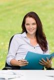 Mulher de negócios no dobrador atrativo do sorriso da natureza Fotografia de Stock Royalty Free