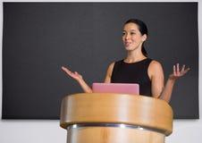 Mulher de negócios no pódio que fala na conferência com a placa fotos de stock