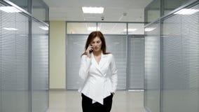 Mulher de negócios no terno que anda e que fala no telefone celular no corredor do escritório video estoque
