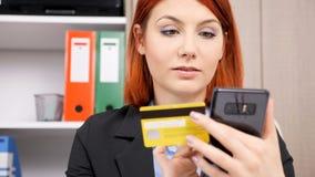 Mulher de negócios no vestuário formal que compra em linha em seu smartphone vídeos de arquivo