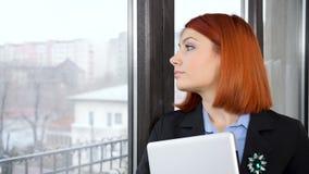 Mulher de negócios no vestuário formal que incorpora o quadro e que olha através da janela fora video estoque