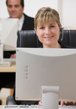 Mulher de negócios nos auriculares que trabalham no computador Fotografia de Stock Royalty Free