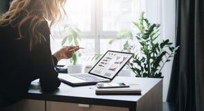 A mulher de negócios nova é tabela próxima ereta, apontando o lápis em gráficos, cartas, diagramas, programações na tela do compu imagens de stock