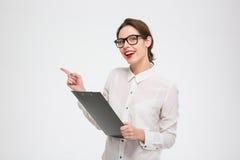 Mulher de negócios nova atrativa de sorriso que guarda a prancheta e que aponta afastado Imagens de Stock