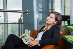 Mulher de negócios nova atrativa que conta dólares e sorriso do dinheiro fotografia de stock