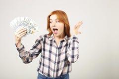 A mulher de negócios nova atrativa que levanta com grupo de USD desconta dentro as mãos que mostram emoções positivas e a express imagens de stock