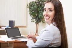 Mulher de negócios nova atrativa que usa o portátil Imagem de Stock Royalty Free