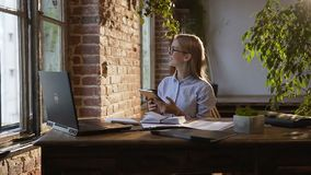 A mulher de negócios nova bem sucedida nos vidros com cabelo longo faz cálculos em seu local de trabalho usando o tablet pc vídeos de arquivo