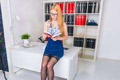 Mulher de negócios nova bonita que senta-se pela mesa de madeira com bloco de notas Trabalhador de escritório moderno no interior Imagem de Stock Royalty Free