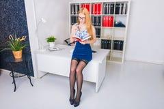 Mulher de negócios nova bonita que senta-se pela mesa de madeira com bloco de notas Trabalhador de escritório moderno no interior Fotografia de Stock