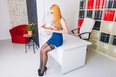 Mulher de negócios nova bonita que senta-se pela mesa de madeira com bloco de notas Trabalhador de escritório moderno no interior Fotos de Stock