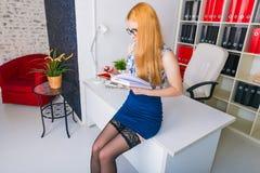 Mulher de negócios nova bonita que senta-se pela mesa de madeira com bloco de notas Trabalhador de escritório moderno no interior Imagens de Stock Royalty Free