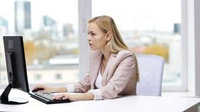 Mulher de negócios nova com computador que datilografa no escritório