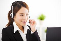 Mulher de negócios nova com os auriculares no escritório fotografia de stock
