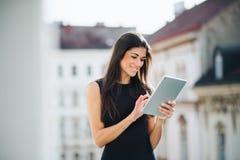 Mulher de negócios nova com a tabuleta que está em um terraço fora de um escritório na cidade fotos de stock royalty free