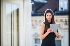 Mulher de negócios nova com a tabuleta que está em um terraço fora de um escritório na cidade foto de stock royalty free