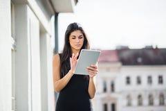 Mulher de negócios nova com a tabuleta que está em um terraço fora de um escritório na cidade foto de stock