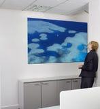 Mulher de negócios nova contemplativa que olha a pintura na parede no escritório Fotos de Stock Royalty Free