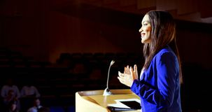 Mulher de negócios nova da misturado-raça que fala no seminário do negócio no auditório 4k vídeos de arquivo