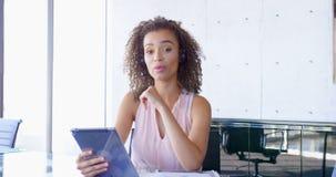 Mulher de negócios nova da raça misturada que fala no fones de ouvido na mesa no escritório 4k filme