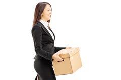 Mulher de negócios nova de sorriso que leva uma caixa Fotos de Stock Royalty Free