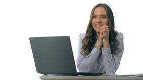 Mulher de negócios nova de sorriso que senta-se em uma tabela do escritório com portátil video estoque