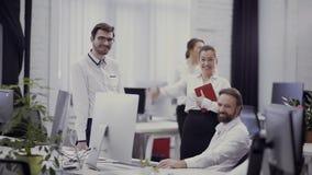 A mulher de negócios nova diz um gracejo a seus colegas no escritório video estoque