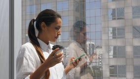 Mulher de negócios nova Drinking Coffee da raça misturada e telefone celular da utilização no escritório perto da janela grande c filme