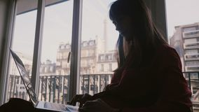 Mulher de negócios nova elegante bonita que usa o portátil na janela da sala com opinião da torre Eiffel na viagem de negócios em video estoque
