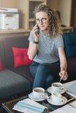 A mulher de negócios nova está sentando-se no sofá na entrada do hotel, café, café bebendo e está falando-se em seu telefone celu Foto de Stock Royalty Free