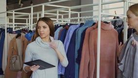 A mulher de negócios nova está usando a tabuleta ao verificar bens em sua loja de roupa O assistente está vindo com vestuário e filme