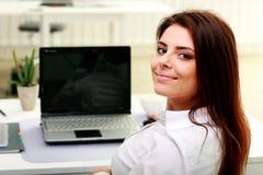 Mulher de negócios nova feliz que senta-se na tabela em seu local de trabalho fotos de stock royalty free