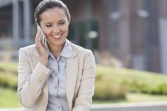 Mulher de negócios nova feliz que usa o telefone celular ao olhar para baixo fora Imagens de Stock Royalty Free