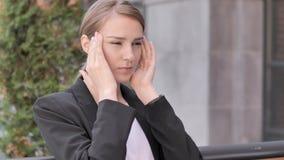 Mulher de negócios nova forçada com o assento da dor de cabeça exterior vídeos de arquivo