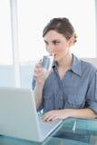 Mulher de negócios nova lindo que bebe um vidro da água que senta-se em sua mesa Imagem de Stock Royalty Free