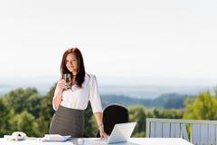 Mulher de negócios nova na tabela ensolarada do escritório da natureza imagem de stock royalty free