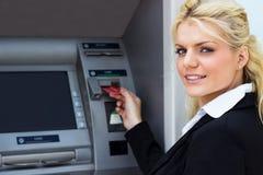 Mulher de negócios nova no ATM imagem de stock