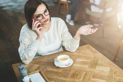 A mulher de negócios nova nos vidros e na camiseta branca está sentando-se no café na tabela de madeira e está falando-se no tele Fotografia de Stock