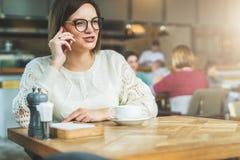A mulher de negócios nova nos vidros e na camiseta branca está sentando-se no café na tabela de madeira e está falando-se no tele Fotos de Stock Royalty Free