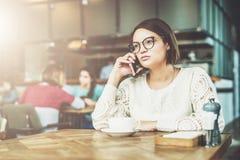 A mulher de negócios nova nos vidros e na camiseta branca está sentando-se no café na tabela de madeira e está falando-se no tele Foto de Stock