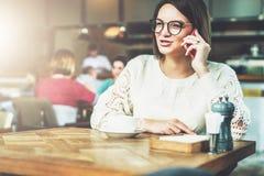A mulher de negócios nova nos vidros e na camiseta branca está sentando-se no café na tabela de madeira e está falando-se no tele Imagens de Stock