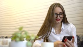 Mulher de negócios nova nos vidros que texting, enviando sms no smartphone, sentando-se no café 4 K Mulher de negócios bonita nov video estoque