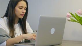 Mulher de negócios nova preocupada que datilografa em seu portátil e que sorri finalmente filme
