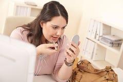 Mulher de negócios nova que aplica o batom no escritório Imagens de Stock